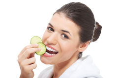 Beautiful woman in bathrobe holding slices of cucumber. Stock Photos