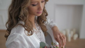 Beautiful woman in bathrobe looking at wedding bouquet stock footage