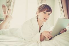 Beautiful woman in bathrobe lying on a bed Royalty Free Stock Photo