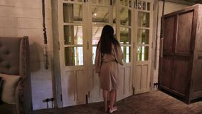 Beautiful woman in bathrobe opens the door to the bathroom. Vintage room and dim light.  stock footage