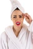Beautiful woman in bathrobe plucks eyebrows Stock Image