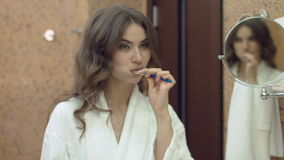 Beautiful woman in the bathrobe standing in the bathroom and brushes her teeth in the morning