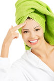 Beautiful woman in bathrobe and turban is touching her forehead. Royalty Free Stock Photography