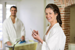 Beautiful woman in bathrobe typing a text message on smartphone. Portrait of beautiful women in bathrobe sitting on kitchen worktop and typing a text message on Royalty Free Stock Images