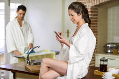 Beautiful woman in bathrobe typing a text message on smartphone. Beautiful women in bathrobe sitting on kitchen worktop and typing a text message on smartphone Royalty Free Stock Photos