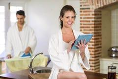 Beautiful woman in bathrobe using digital tablet Stock Photos
