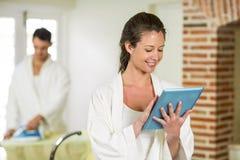 Beautiful woman in bathrobe using digital tablet Royalty Free Stock Photography