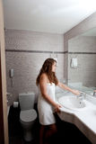 Beautiful woman in bathroom. Dressed in towel beautiful woman staying at modern bathroom royalty free stock photos