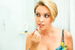 Beautiful woman in bathroom applying lipstick Royalty Free Stock Photo