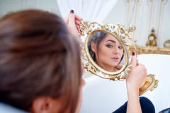 Beautiful woman in the bathroom looking in the mirror Royalty Free Stock Images
