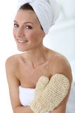 Beautiful woman in bathroom with rubbing glove Royalty Free Stock Photo