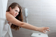 Beautiful woman in bathroom streching for somethin Royalty Free Stock Images