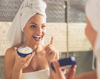 Beautiful woman in bathroom. Beautiful young woman in bath towel is applying cream on her face and smiling while looking into the mirror in bathroom Royalty Free Stock Image