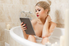 Beautiful woman in a bathtub with a tablet PC. Stock Photography
