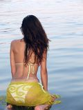 Beautiful woman on the beach. Beautiful woman kneeling in the sea water Royalty Free Stock Photography