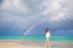 Beautiful happy woman on the beach with beautiful rainbow over the sea. Beautiful woman on the beach with beautiful rainbow over the sea Royalty Free Stock Photo