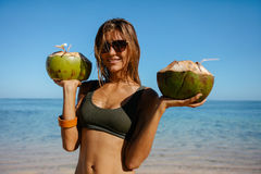 Beautiful woman on the beach with fresh coconuts Stock Photography