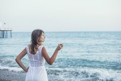 Beautiful woman on the beach with a glass of wine in white dress Royalty Free Stock Photography