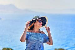 Beautiful woman in beach hat enjoying sea view with blue sky at sunny day in Bodrum, Turkey. Vacation Outdoors Seascape Summer. Beautiful woman in beach hat royalty free stock photo