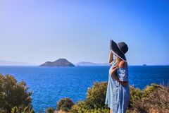 Beautiful woman in beach hat enjoying sea view with blue sky at sunny day in Bodrum, Turkey. Vacation Outdoors Seascape Summer stock photo