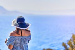 Beautiful woman in beach hat enjoying sea view with blue sky at sunny day in Bodrum, Turkey. Vacation Outdoors Seascape Summer. Beautiful woman in beach hat royalty free stock images