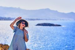 Beautiful woman in beach hat enjoying sea view with blue sky at sunny day in Bodrum, Turkey. Vacation Outdoors Seascape Summer. Travel Concept stock image
