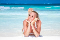 Beautiful woman on the beach. Lying down and tanning on a white sandy seashore, enjoying summer vacation on a tropical beach resort Royalty Free Stock Image