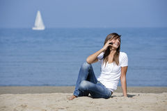 Beautiful woman at the beach with a mobile phone Royalty Free Stock Images