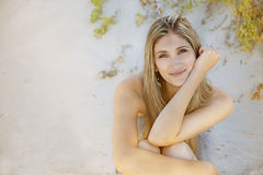 Beautiful woman on a beach on a sunny day. Sitting on the sand Stock Image