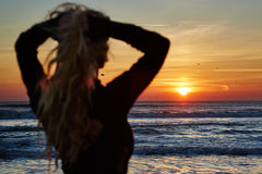 Beautiful woman on the beach at sunrise Stock Image