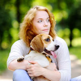 Beautiful woman with Beagle dog. Young beautiful woman playing with Beagle dog in the summer park Royalty Free Stock Image