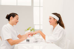 Beautiful woman with beautician applying nail varnish to female clients nails Stock Images