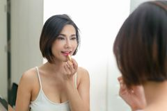 Beautiful woman with beauty face, Lips applying lip balm. royalty free stock image