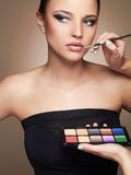 Beautiful woman. beauty girl with make-up.Makeup artist applies lipstick Royalty Free Stock Images
