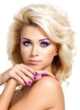 Beautiful woman with beauty purple manicure and makeup of eyes. Royalty Free Stock Image