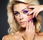 Beautiful woman with beauty purple manicure and makeup of eyes. royalty free stock photo