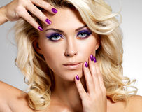 Beautiful woman with beauty purple manicure and makeup of eyes. Royalty Free Stock Images