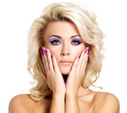 Beautiful woman with beauty purple manicure and makeup of eyes. Beautiful blond woman with beauty purple manicure and makeup of eyes. Fashion model with curly stock image