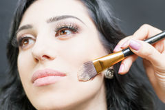 Beautiful woman at beauty salon receives makeup Stock Image