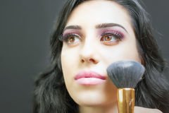 Beautiful woman at beauty salon receives makeup Stock Images