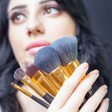 Beautiful woman at beauty salon with set of makeup brushes. Beautiful arabian woman at beauty salon with a nice makeup. Holding in hands a set of professional Stock Image