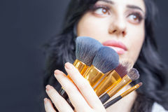 Beautiful woman at beauty salon with set of makeup brushes. Beautiful arabian woman at beauty salon with a nice makeup. Holding in hands a set of professional Stock Photo