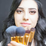 Beautiful woman at beauty salon with set of makeup brushes Royalty Free Stock Photography