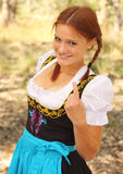 Beautiful Woman Beckoning. Beautiful red-head woman wearing a traditional bavarian dirndl dress beckoning to come here Stock Image