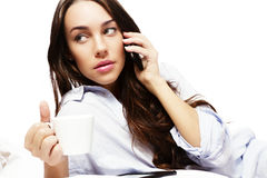 Beautiful woman in bed holding coffee while callin Royalty Free Stock Images