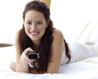 Beautiful woman in bed holding a remote Royalty Free Stock Photos