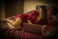 Beautiful woman in bed with laptop, in red nightdress Stock Photos
