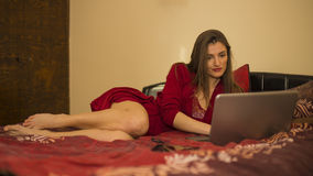 Beautiful woman in bed with laptop, in red nightdress Stock Photography