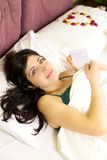 Beautiful woman in bed with love letter from boyfriend Royalty Free Stock Photo