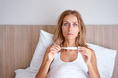 Beautiful woman in bed. Morning fever. Upset young beautiful woman sitting at bed holding thermometer Royalty Free Stock Photography